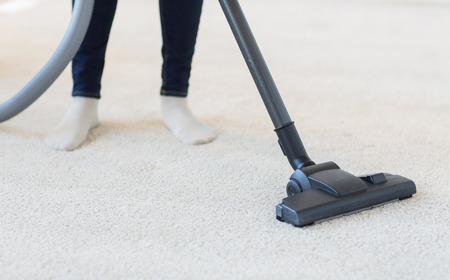 mujer limpiando: las personas, el trabajo doméstico y de limpieza concepto - cerca de la mujer con las piernas aspiradora limpieza de alfombras en casa Foto de archivo