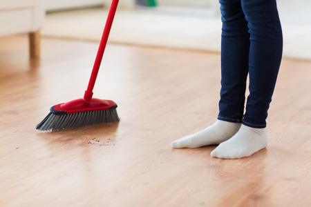 orden y limpieza: las personas, el trabajo doméstico, la limpieza y el servicio de limpieza concepto - cerca de piernas de la mujer con la escoba Suelo arrebatador en casa