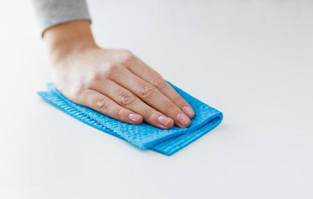mensen, huishoudelijk werk en het huishouden concept - close-up van de vrouw de hand reinigen tafel oppervlak met doek thuis Stockfoto