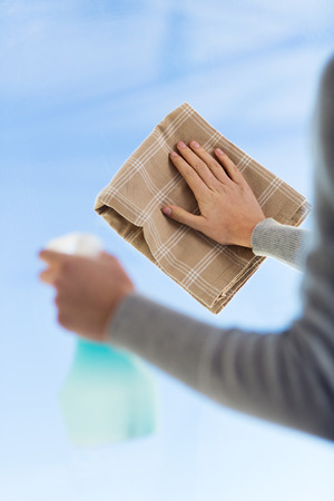 people, housework and housekeeping concept - close up of woman hands cleaning window glass with cloth and spray detergent photo