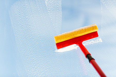 people, housework and housekeeping concept -close up of hand cleaning window glass with sponge mop and foam Stockfoto