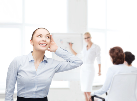 bruit: business, office and gossip concept - smiling businesswoman listening gossig at office