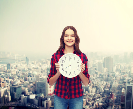 o'clock: happiness and people concept - smiling young woman in casual clothes with wall clock showing 8 oclock