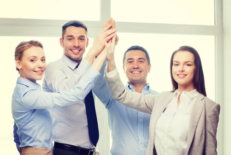 hands high: success, business, office and winning concept - happy business team giving high five in office Stock Photo