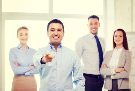 invitando: concepto de negocio y la oficina - sonriendo apuesto hombre de negocios con equipo de oficina apuntando con el dedo a usted