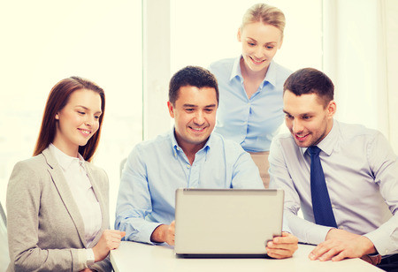people: business and office concept - smiling business team working with laptop computer in office