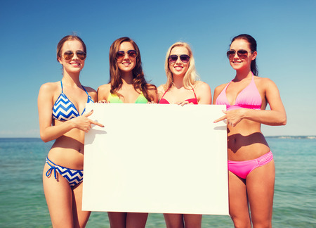young bikini: summer vacation, holidays, travel, advertising and people concept - group of smiling young women with big white blank billboard on beach