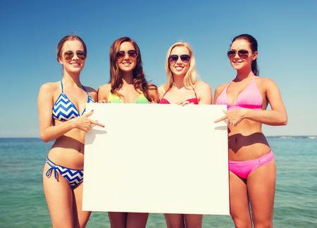 niñas en bikini: verano, vacaciones, viajes, publicidad y concepto de la gente - grupo de mujeres jóvenes sonriendo con gran cartel en blanco blanco en la playa