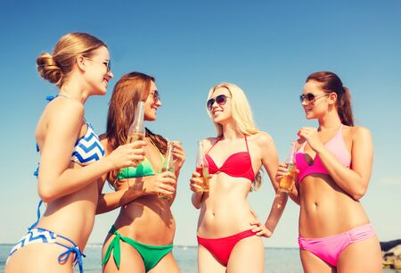 non alcoholic beer: summer vacation, holidays, travel and people concept - group of smiling young women sunbathing and drinking on beach