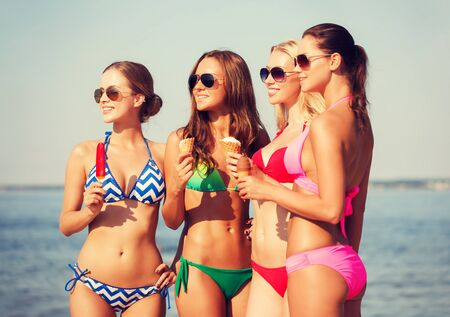 woman ice cream: summer vacation, holidays, food, travel and people concept - group of smiling young women eating ice cream on beach