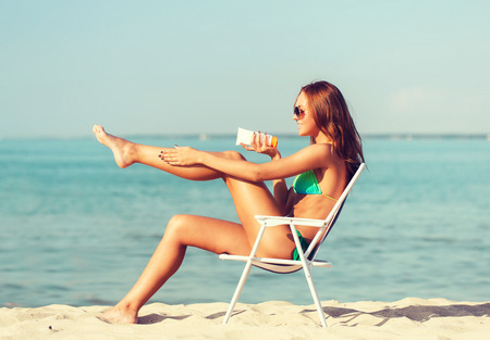 chilling: summer vacation, holidays and people concept - smiling young woman sunbathing in lounge on beach
