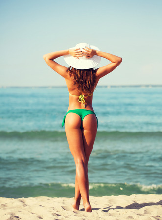 summer vacation, holidays and people concept - young woman sunbathing on beach Imagens