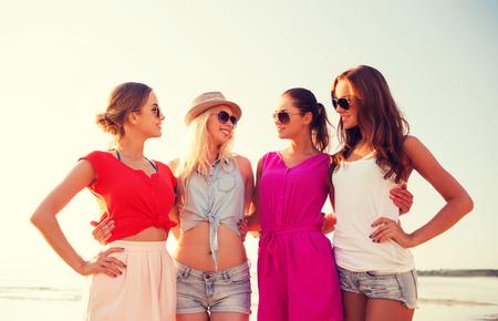 despedida de soltera: las vacaciones de verano, las vacaciones, los viajes y el concepto de la gente - grupo de mujeres jóvenes sonrientes en gafas de sol y ropa casual en la playa