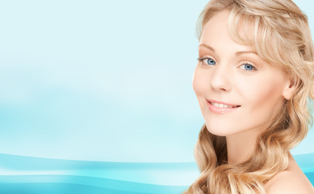beauty, people, hair care and health concept - beautiful young woman face with long wavy hair over blue background Stock Photo