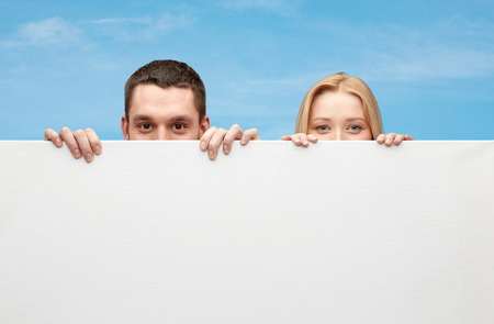 big behind: people, advertisement and information concept - happy couple hiding behind big white blank board over blue sky background