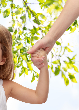 people, charity, family and adoption concept - close up of woman and little girl holding hands over green tree leavers background