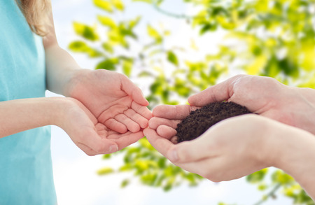 legacy: people, charity, family and legacy concept - close up of father and girl holding soil in cupped hands over green nature background