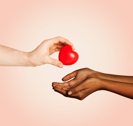 love, charity, valentines day, donation and international concept - close up of man hand giving heart to woman over beige background photo