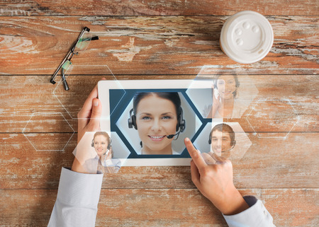 helpline: business, people, communication and technology concept - close up of hands pointing finger to tablet pc computer screen with helpline operator image, coffee cup and eyeglasses on table Stock Photo