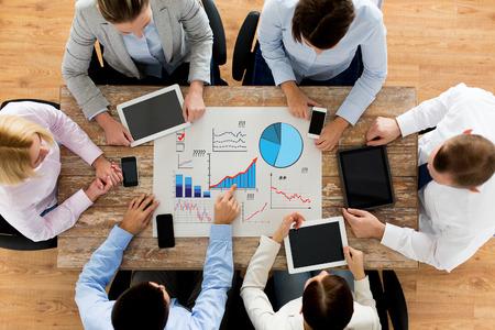 het bedrijfsleven, mensen, statistieken en teamwork concept - close-up van het creatieve team met grafieken op papier, smartphones en tablet pc computers zitten aan tafel in het kantoor Stockfoto