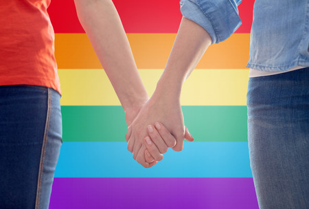 same sex: people, homosexuality, same-sex marriage, gay and love concept - close up of happy lesbian couple holding hands over rainbow flag background Stock Photo