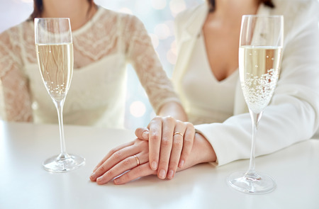 same sex: people, homosexuality, same-sex marriage, celebration and love concept - close up of happy married lesbian couple hands on top and champagne glasses over holiday lights background