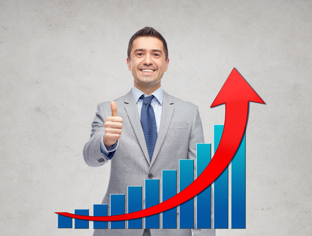 business, people, gesture and success concept - happy smiling businessman in suit with growing chart showing thumbs up over gray background photo