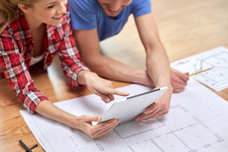 new look: repair, building, renovation, architecture and technology concept - close up of couple with tablet pc and blueprint at home