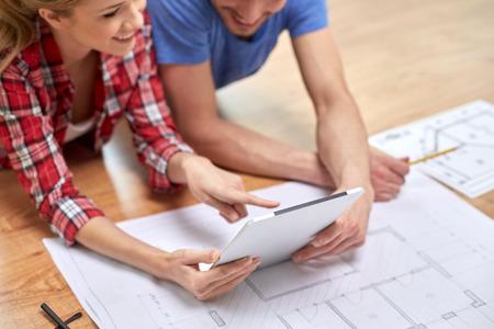 pareja en casa: reparación, construcción, renovación, la arquitectura y la tecnología concepto - cerca de la pareja con tablet pc y el modelo en casa