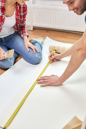 repair, building and people concept - close up of happy couple with ruler measuring wallpaper at home photo