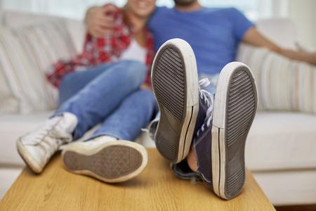 beweglichen, zu Hause, Reparatur und Menschen Konzept - Nahaufnahme von Paar Beine entspannende und mit den Beinen auf dem Tisch sitzt auf dem Sofa in der neuen Wohnung Standard-Bild