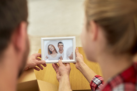 family memories: people, family, memories and moving concept - close up of happy couple looking at photo and unpacking things at new home
