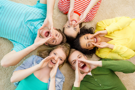 5: education and happiness concept - group of young smiling people lying down on floor in circle screaming and shouting Stock Photo
