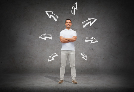 many hands: choice, direction, possibilities and people concept - smiling man in white t-shirt with crossed arms over arrow doodles and concrete background Stock Photo