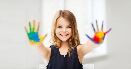 vzdělání, školy, umění a painitng koncept - malá studentka ukazuje namalované rukou na škole Reklamní fotografie