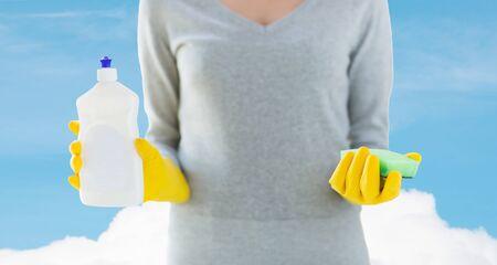 orden y limpieza: las personas, las tareas dom�sticas, lavar los platos y la limpieza concepto - cerca de la mujer que sostiene una esponja y botella de limpiador sobre el cielo azul y nubes de fondo