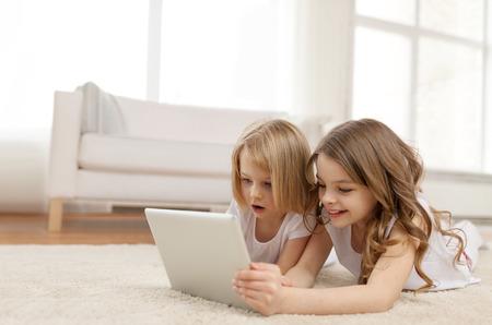 technology: i bambini, la tecnologia e il concetto di casa - due bambine con il computer tablet pc sdraiato sul pavimento a casa
