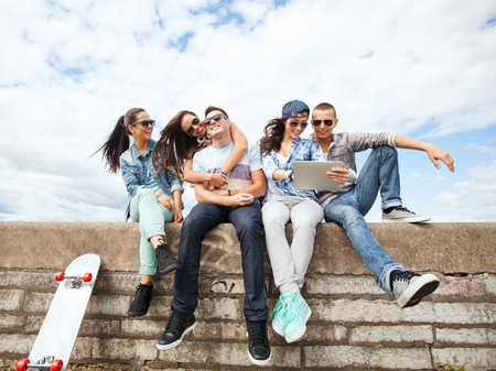 chilling: summer holidays, teenage and technology concept - group of teenagers looking at tablet pc
