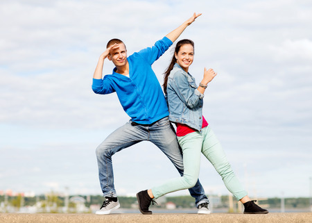 urban dance: summer holidays, teenage and dancing concept - couple of teenagers dancing outside