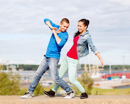 hip hop girl: summer holidays, teenage and dancing concept - couple of teenagers dancing outside