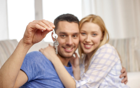 key: love, people, real estate, home and family concept - smiling couple showing keys over living room background Stock Photo