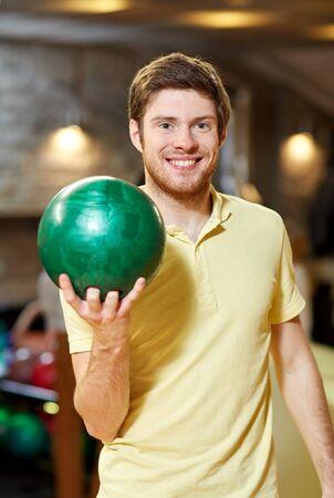 bolos: la gente, el ocio, el deporte y el concepto de entretenimiento - hombre joven feliz que sostiene la bola en club del bowling