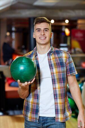 amateur: la gente, el ocio, el deporte y el concepto de entretenimiento - hombre joven feliz que sostiene la bola en club del bowling