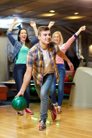 people, leisure, sport and entertainment concept - happy young man throwing ball in bowling club photo