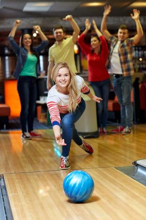 人、レジャー、スポーツ、エンターテイメントのコンセプト - ボウリング クラブでボールを投げて幸せな若い女