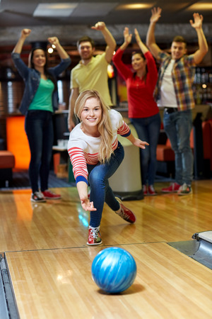 team sports: people, leisure, sport and entertainment concept - happy young woman throwing ball in bowling club