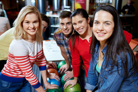 people, leisure, sport, friendship and entertainment concept - happy friends in bowling club