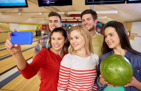 people, leisure, sport, friendship and entertainment concept - happy friends taking selfie with smartphone in bowling club photo