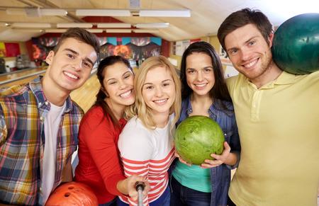 bolos: la gente, el ocio, el deporte, la amistad y el concepto de entretenimiento - amigos felices que toman Autofoto con smartphone en monopod en club del bowling Foto de archivo