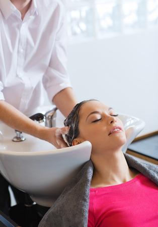 Schönheit und Personen Konzept - glückliche junge Frau mit Friseur Waschkopf an Friseursalon
